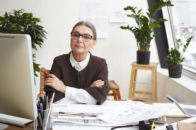 Concepto de trabajo, ocupación y profesión. arquitecta atractiva experimentada en gafas que trabaja en la oficina en casa, haciendo dibujos en su escritorio, usando computadoras, calculadoras y herramientas de ingeniería