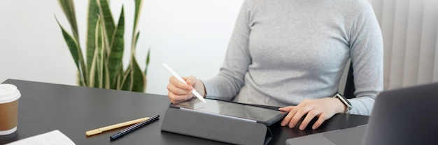Concepto de trabajo de oficina una funcionaria usando su tableta para trabajar en un trabajo de documento en la oficina.