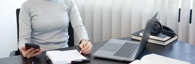 Concepto de trabajo de oficina una funcionaria usando un teléfono móvil para verificar la agenda de la reunión para mañana.