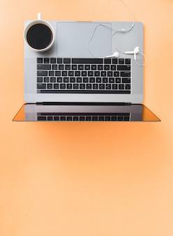Concepto de trabajo remoto portátil con taza de café y auriculares