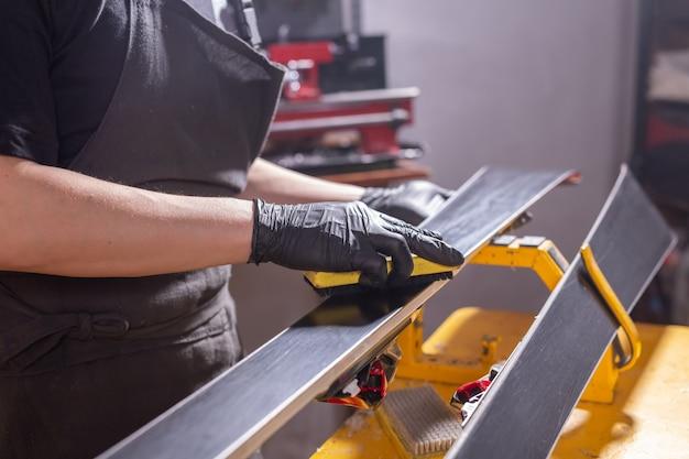 Concepto de trabajo y reparación: manos de un hombre reparando el esquí frotando una parafina
