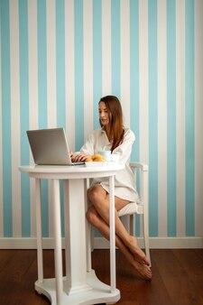 Concepto de trabajo, tecnología y personas remotas. feliz hermosa mujer trabajando con ordenador portátil en la oficina en casa