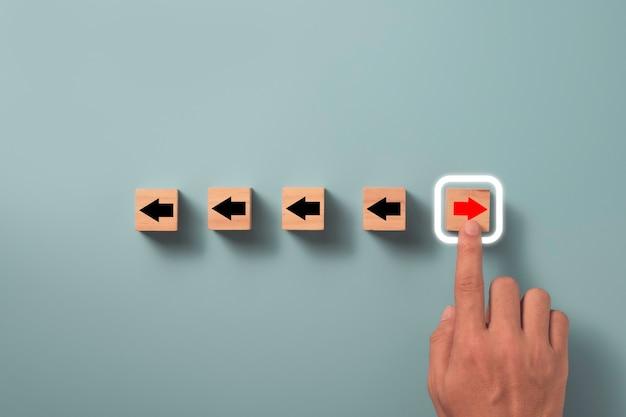 Concepto de transformación de disrupción y tecnología, mano tocando la flecha roja en el cubo de bloque de madera salir de la flecha negra sobre fondo azul.