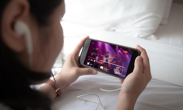 Concepto de transmisión de video en vivo manos femeninas que sostienen el teléfono móvil