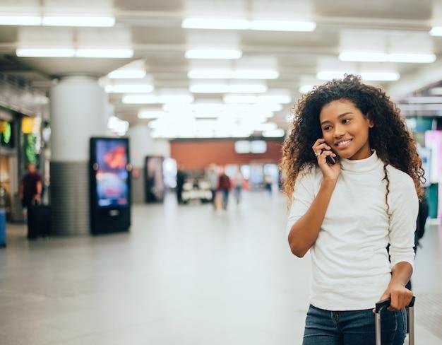 Concepto del transporte aéreo con la mujer de negocios casual joven que habla en el teléfono.