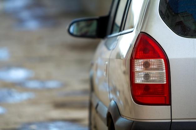 Concepto de transporte, conducción y vehículos de motor: detalle de vista posterior de cerca de luces rojas de parada y espejo del nuevo y lujoso auto plateado brillante en una escena colorida borrosa.