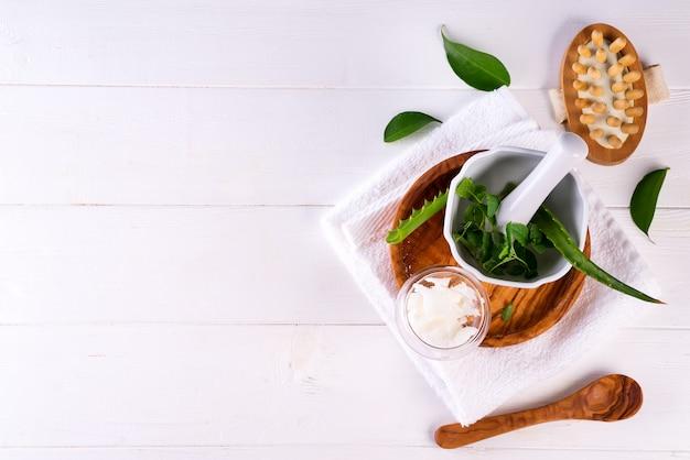 Concepto de tratamiento de spa con aloe vera, productos cosméticos naturales y cepillo de masaje sobre madera blanca.