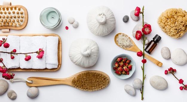 Concepto de tratamiento de spa, composición plana con productos cosméticos naturales y cepillos de masaje.