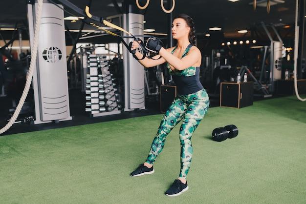 Concepto trx. bella dama ejercitando sus músculos con la ayuda de la honda del entrenador de suspensión o las correas de suspensión en el gimnasio