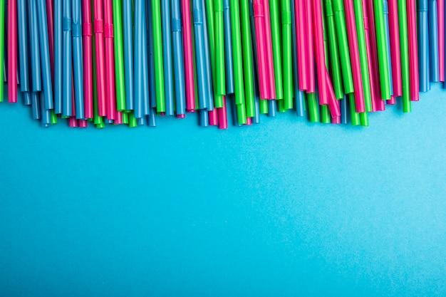 Concepto de tubos de plástico. pajas de cóctel de varios colores sobre un fondo azul