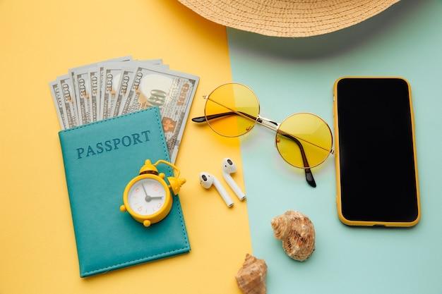 Concepto de turismo. accesorios de viaje y pasaporte con dinero en superficie azul amarillo