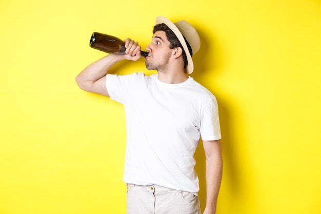 Concepto de turismo y vacaciones. hombre bebiendo vino de botella en vacaciones, de pie contra el fondo amarillo