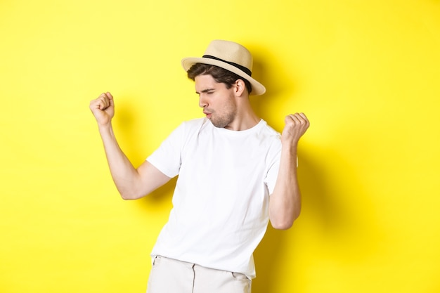 Concepto de turismo y vacaciones. turista afortunado regocijándose, haciendo puñetazos y diciendo que sí, de pie satisfecho contra el fondo amarillo.