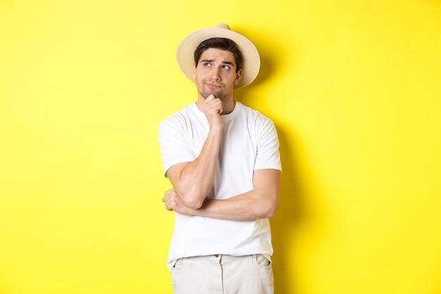 Concepto de turismo y verano. turista de hombre pensativo reflexionando, mirando la esquina superior izquierda y pensando, de pie con sombrero de paja y camiseta blanca sobre fondo amarillo.