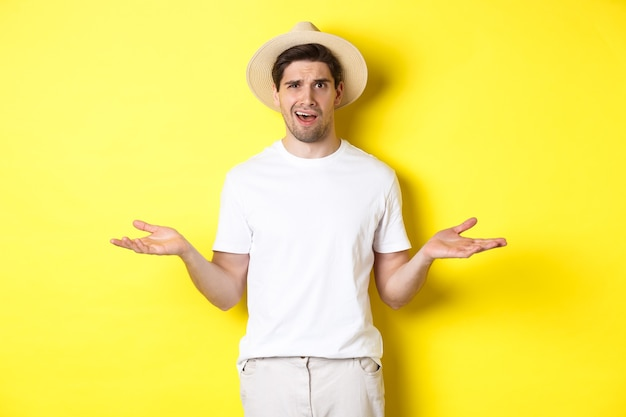 Concepto de turismo y verano. viajero chico confundido encogiéndose de hombros, no puedo entender algo, de pie contra el fondo amarillo