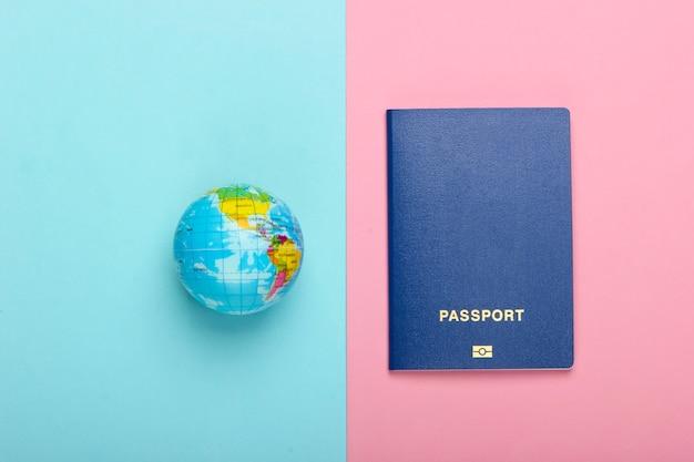 Concepto de turismo y viajes. globo y pasaporte en una pared azul-rosa pastel vista superior