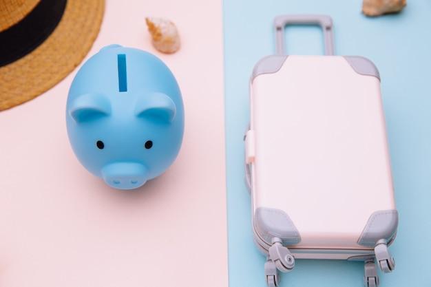 Concepto de turismo y viajes. mini maleta de equipaje de viaje, sombrero y hucha en primer plano de superficie rosa azul