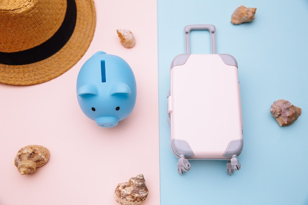 Concepto de turismo y viajes. mini maleta de equipaje de viaje, sombrero y hucha en superficie rosa azul