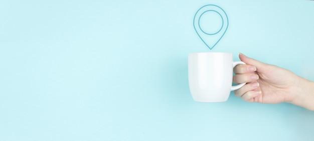 Concepto de ubicación de dirección de pin. mano de niña sostenga la taza de café de la mañana con el icono de marcador de ubicación de signo sobre fondo azul. concepto de navegación y mapas de internet.
