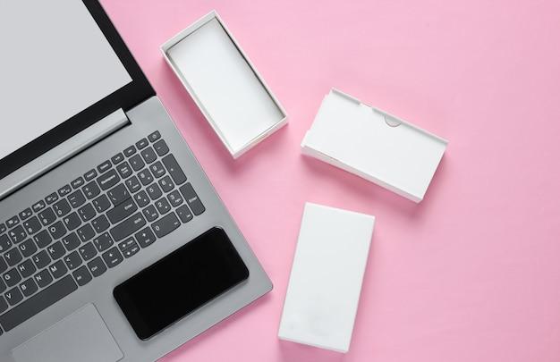 El concepto de unboxing, techno blogging. caja con un nuevo teléfono inteligente, portátil en superficie en colores pastel.