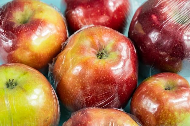 Concepto de uso excesivo de plástico: manzanas frescas en papel de cocina.