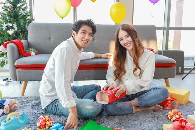 Concepto de vacaciones de año nuevo y navidad. el retrato de la mujer asiática sonriente del hombre hace una caja de regalo y adorna la sala de estar para la fiesta de navidad.