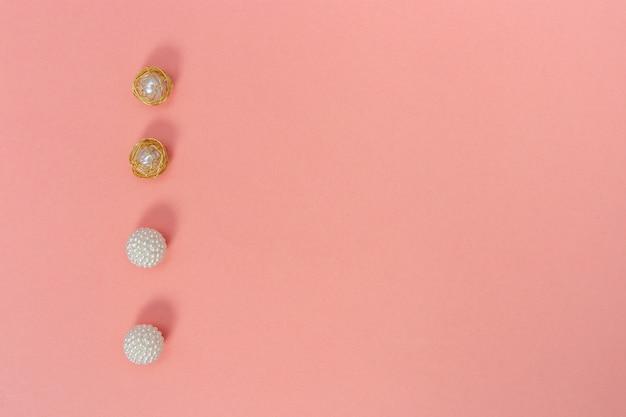 Concepto de vacaciones para la boda o el día de san valentín. decoración de cuentas en papel de color rosa pastel con espacio de copia. composición de estilo minimalista.