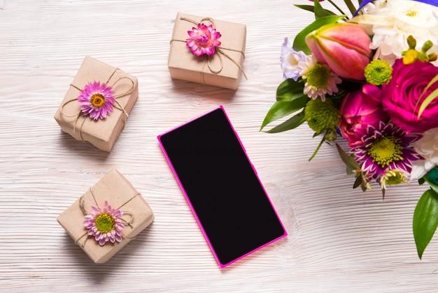 Concepto de vacaciones, cajas de regalo y teléfonos inteligentes.