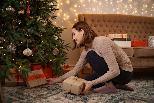 Concepto de vacaciones, celebración y personas de invierno - cerca de mujer poniendo presente bajo el árbol de navidad