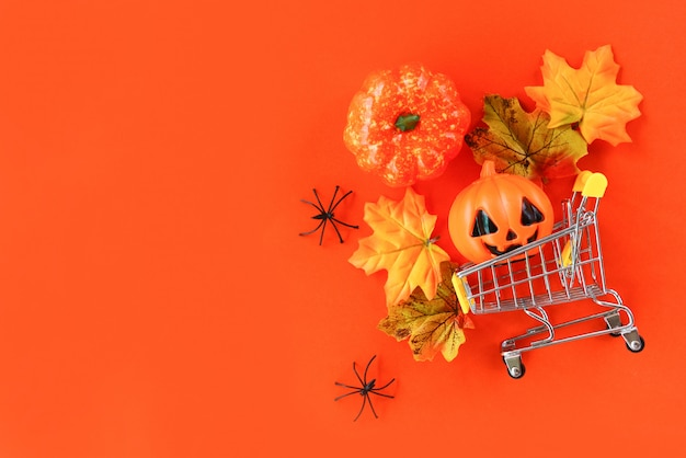 Concepto de vacaciones de compras de halloween / accesorios con araña calabaza jack o linterna y hojas de otoño en un carrito de compras en vista superior de fondo naranja