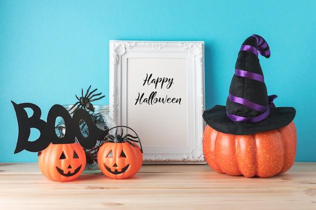 Concepto de vacaciones con decoración de calabaza de halloween y marco de fotos en la mesa de madera