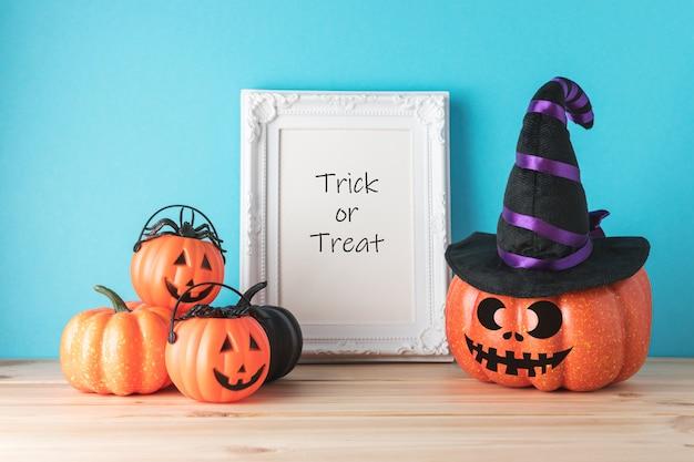 Concepto de vacaciones con divertida decoración de calabaza de halloween y marco de fotos en la mesa de madera