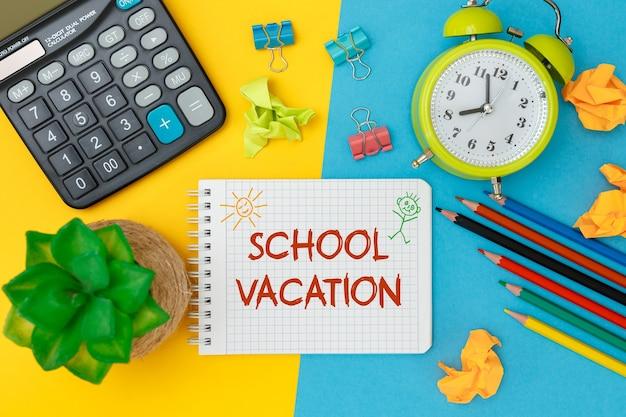 Concepto de vacaciones escolares. cuaderno abierto con útiles escolares