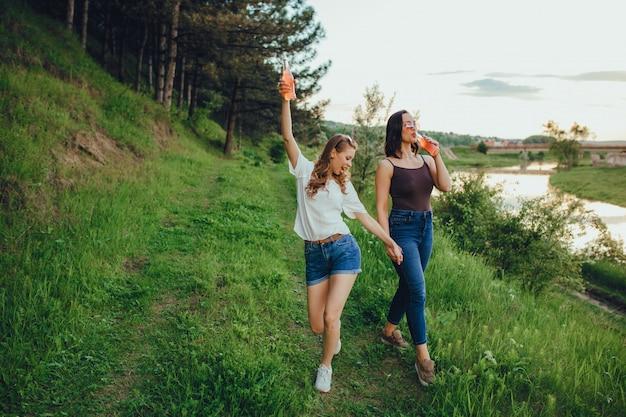 Concepto de vacaciones y felicidad, dos chicas se divierten, beben cócteles de la botella, diversión de verano, al atardecer, expresión facial positiva, al aire libre