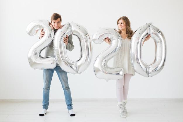 Concepto de vacaciones, fiesta y fiesta: la feliz pareja amorosa besa y sostiene globos plateados 2020. celebración de año nuevo
