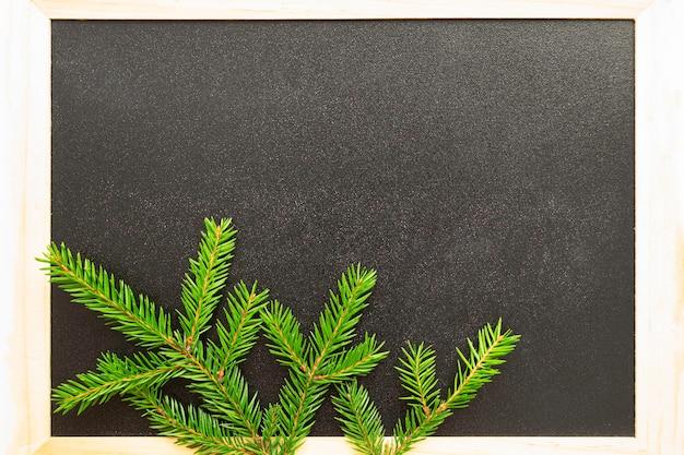 Concepto de vacaciones de invierno y año nuevo. pizarra negra en un marco de madera y una rama de un árbol en la esquina. lugar para texto, espacio de copia.