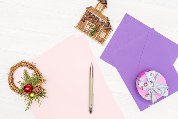 Concepto de vacaciones de invierno la hoja de papel en blanco sobre la mesa de madera blanca con un bolígrafo y sobres