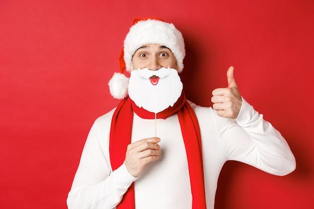 Concepto de vacaciones de invierno de navidad y celebración retrato de hombre divertido con sombrero de santa sosteniendo oso ...