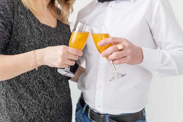 Concepto de vacaciones, navidad, día de san valentín y año nuevo: la mujer y el hombre celebran y sostiene el vino en un vaso de cerca sobre fondo blanco.