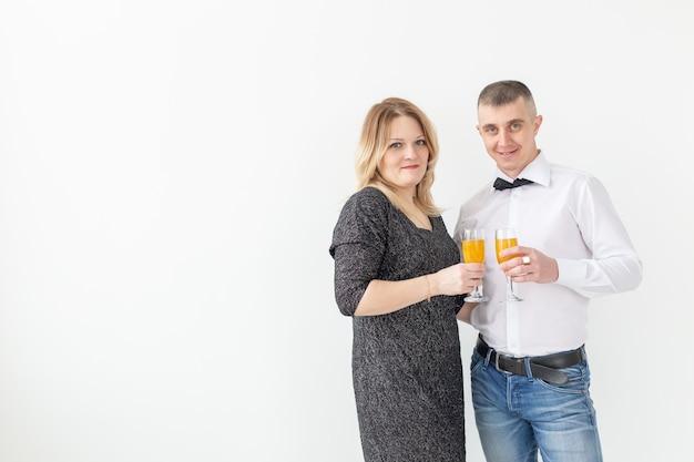 Concepto de vacaciones, navidad, día de san valentín y año nuevo: la mujer y el hombre celebran y sostiene el vino en un vaso sobre fondo blanco con espacio de copia