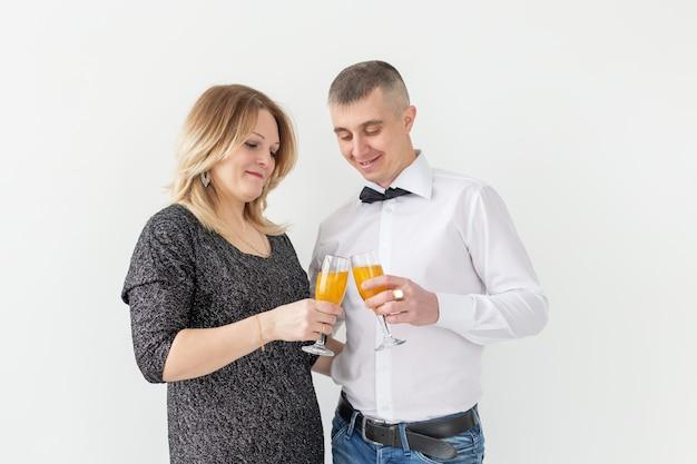 Concepto de vacaciones, navidad, día de san valentín y año nuevo: la mujer y el hombre celebran y sostiene el vino en un vaso sobre fondo blanco.