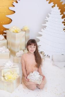 Concepto de vacaciones de navidad. niña en vestido dorado sentado junto a árbol de navidad con regalo.