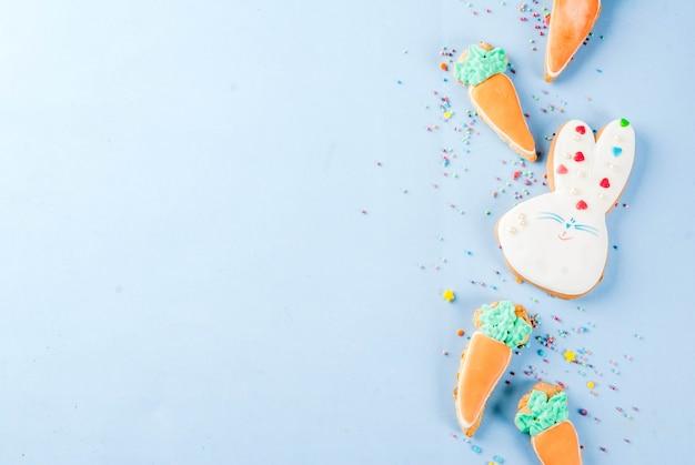 Concepto de vacaciones de pascua, galletas dulces en forma de zanahorias, conejito de pascua, con chispitas dulces, fondo azul claro copia espacio vista superior, fondo de tarjeta de felicitación