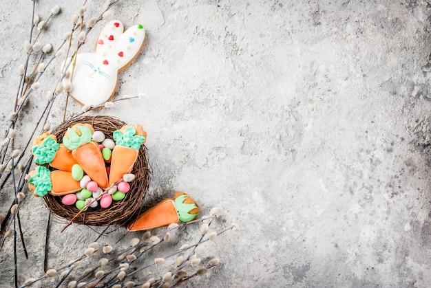 Concepto de vacaciones de pascua, galletas dulces en forma de zanahorias, conejito de pascua, con huevos de colores, vista superior, espacio de copia de fondo de piedra gris