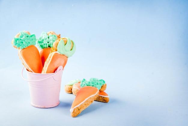 Concepto de vacaciones de pascua, galletas dulces en forma de zanahorias, fondo azul claro copia vista superior del espacio, fondo de la tarjeta de felicitación