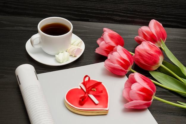 Concepto de vacaciones. ramo de tulipanes rosados, una taza de café, galletas rojas en forma de corazón con una nota, revista vacía
