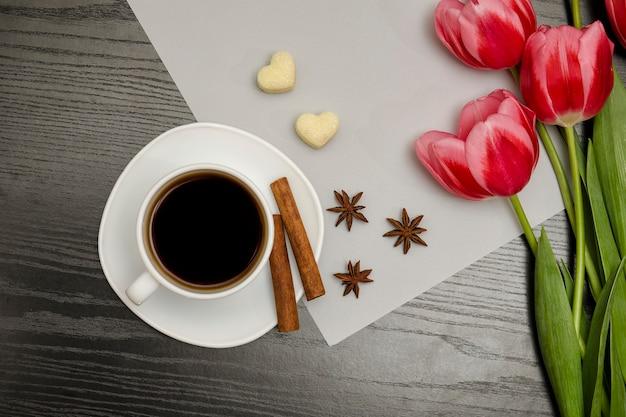Concepto de vacaciones. ramo de tulipanes rosados, una taza de café.