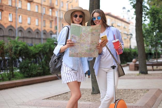 Concepto de vacaciones y turismo: chicas guapas en busca de dirección en la ciudad.