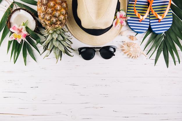 Concepto de vacaciones de vacaciones de verano. accesorios para viaje y frutas exóticas en mesa de madera blanca. vista superior y endecha plana.