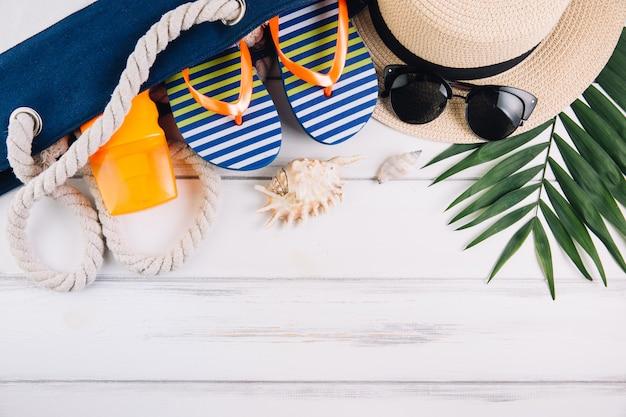 Concepto de vacaciones de vacaciones de verano. bolsa de playa y accesorios en mesa de madera blanca. vista superior y endecha plana.